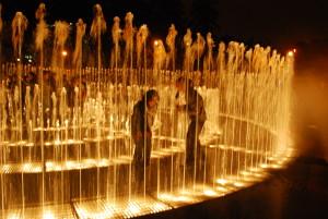 Parque das aguas, na foto duas pessoas brincam no meio de uma fonte que jorra jatos de agua do chão