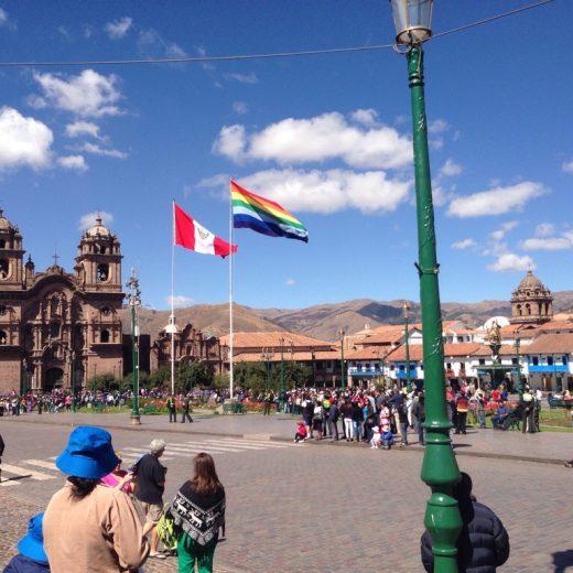 Praça de armas de Cusco. Céu azul com poucas nuvens e duas bandeiras - a de Cusco e a do Peru - flamejantes com o vento, além de pessoas esperando para assistir a um desfile.