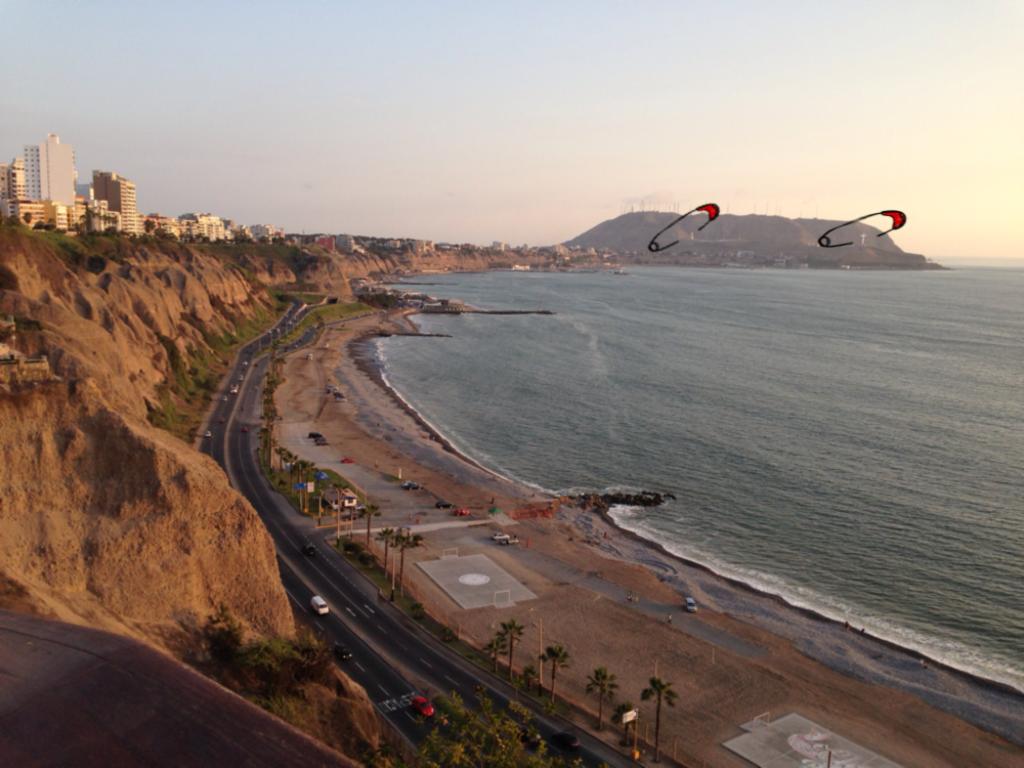 Fotografia da paisagem de Lima, o mar e a costa com as falésias e ao fundo o morro do bairro de chorrillos. Está um dia de sol e é possível visualizar bem a paisagem