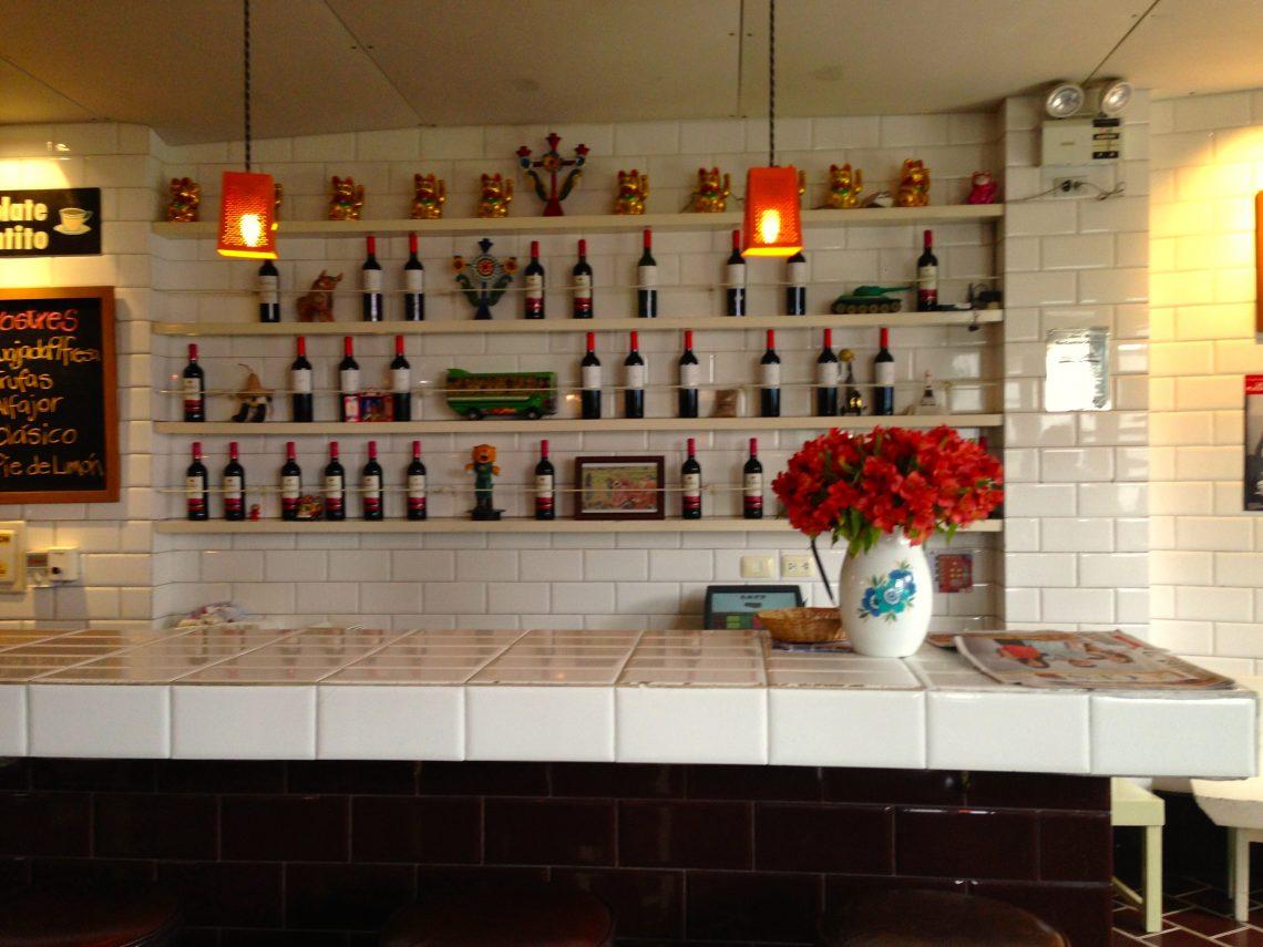 Entrada do restaurante LA 73, um balcão de azulejo branco e sobre ele um vaso com flores vermelhas. Na parede, estantes com diversos vinhos