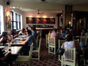Salão principal do restaurante LA 73. Chão de ladrilhos escuros, cadeiras de madeira e cor clara e nas paredes diversos quadros, com um ar um pouco anos 50.