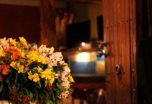 arranjo com flores amarelas e brancas, ao fundo a porta do restaurante huaca pucllana em madeira rústica