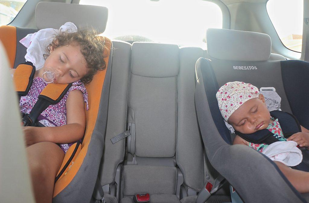 """As meninas fazendo a """"siesta"""" no carro a caminho da praia."""