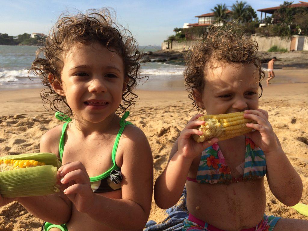 Olivia aprendendo a comer milho na praia, com a prima, na casa dos avós.